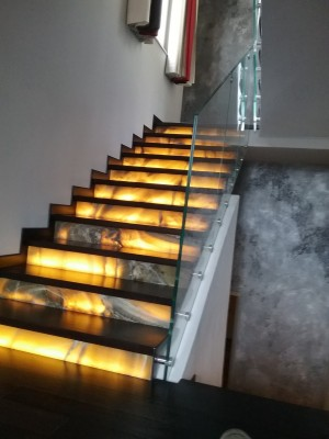Glass railings to protect internal staircase made of stone and Onyx